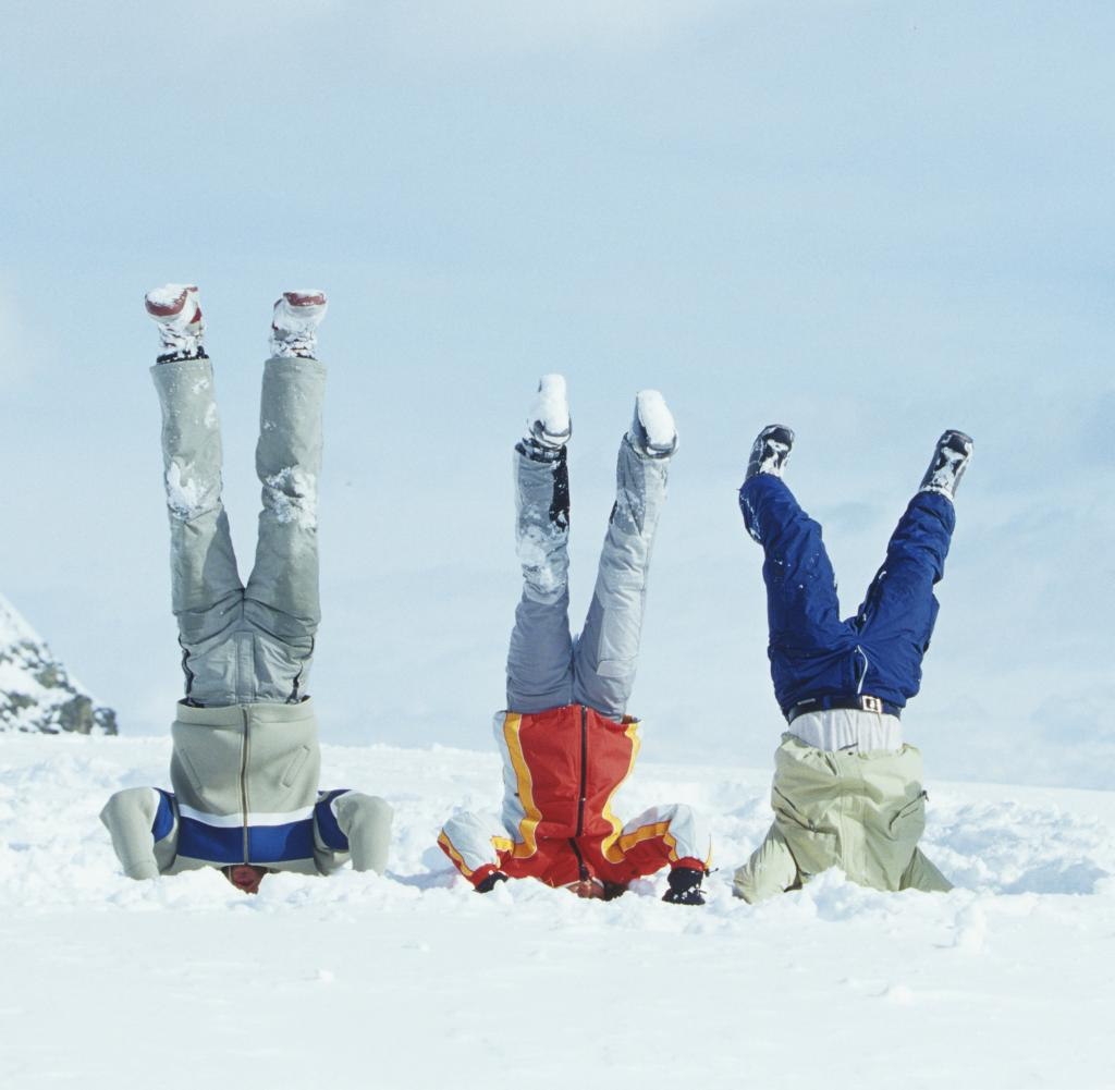 group of three friends doing head stand in snow
